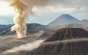 Bromo Erupting with Semeru Volcano as the Background